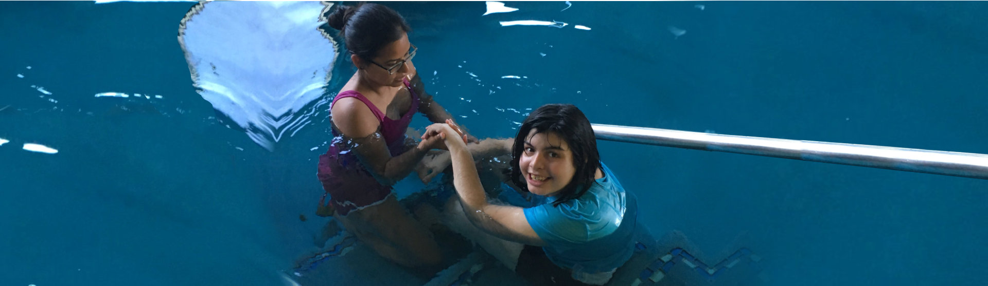 woman teaching a young girl to swim