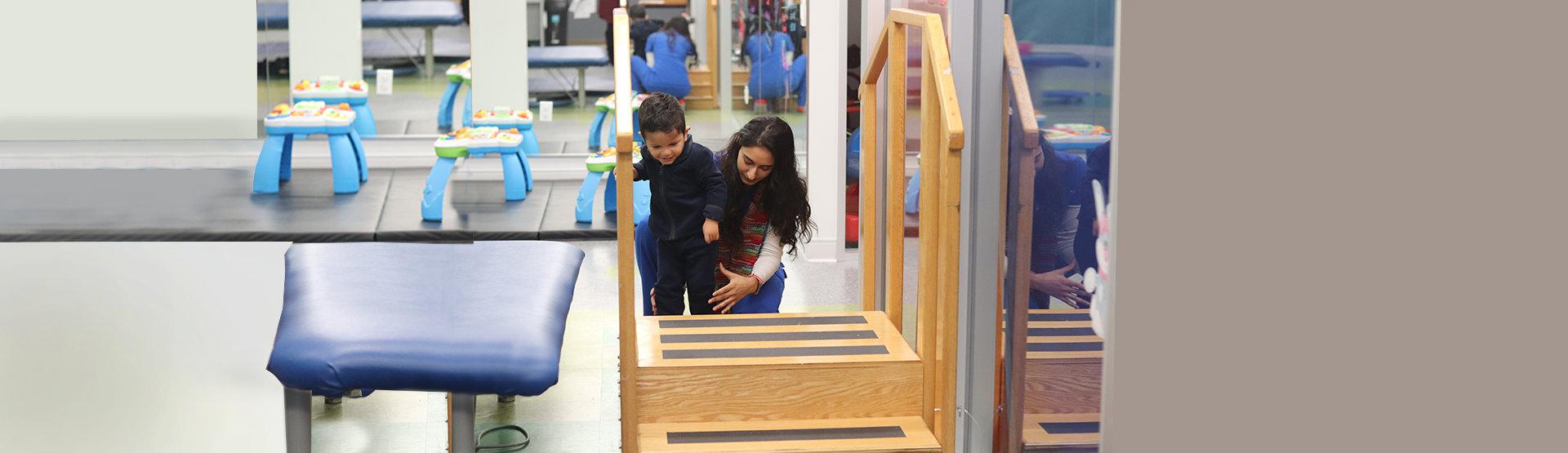 teacher guiding a little boy in walking
